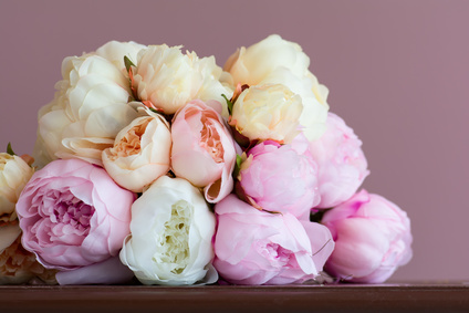 Bouquet made of artifical pink peony laying on a  wood surface. Shot against pink wall background. Shallow DOF.