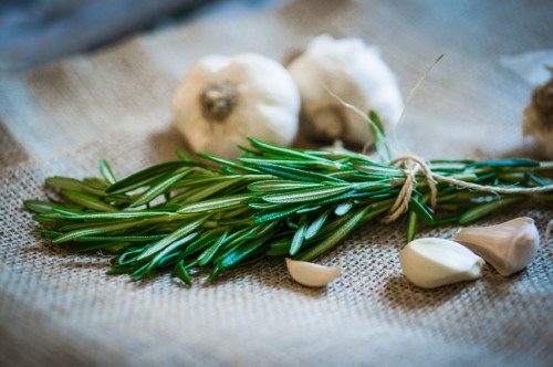 Fresh rosemary with fresh garlic on wooden background