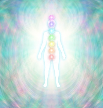 Chakra Energy Balancing  -  Soft pastel colored energy field around a white female silhouette with a turquoise glow, with seven chakras aligned centrally from crown to root